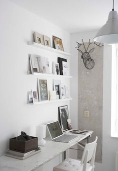 A beautiful idea for a home office - thin white shelves with images and books, a well worn white table used as a desk - so calm and eclectic.
