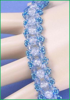 "Jewelry is made with small beads. Some are glass or stone. Adult supervision is recommended. This bracelet is made with Miyuki 11/0 sl sapphire blue glass seed beads along with 4mm light blue Chinese crystal bicone glass beads and, is accented with 6mm light blue round crackle glass beads and hooks with a toggle clasp. Measures approx. 6 3/4"" long (including clasp) by 5/8"" wide and is a design pattern from: Deborah Roberti. Priced at only $21.00 with ""FREE SHIPPING."""