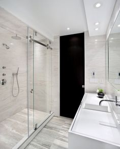 Modern bathroom with rolling glass barn door shower.