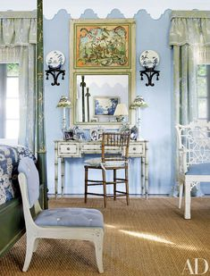 In designer Nancy Morton's Florida home, painted furniture and a blue, white, and green palette freshen the master bedroom. Brackets from John Rosselli hang above a Louis J. Solomon faux-bamboo desk with custom-painted decoration by Bob Christian; the curtain fabric is by Brunschwig & Fils, a Clarence House stripe covers the slipper chair, and the sea-grass carpet is by Stark.