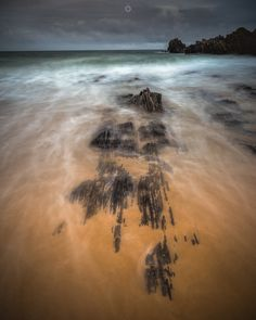 Creeping In - A long exposure, landscape image of waves rolling over the sand on Sunnyside Beach in Morayshire, Scotland.