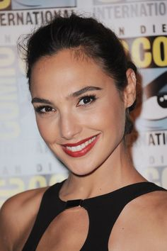 Keeping her hair in a braided up do with a light contour on the cheekbones and a coral red lip, Gadot attends the Entertainment Weekly: Women Who Kick Ass panel during Comic-Con International 2015.