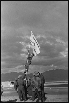 Captain Avraham Adan raises a handmade Israeli ink flag at Eilat, signifying the end of the 1948 Arab-Israeli War of Independence.