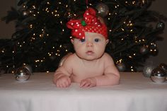 DIY Christmas baby Photo.  Christmas tree, table with white blanket and silver ornaments.