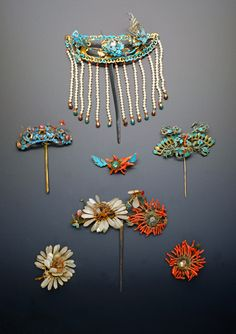 FOUR CHINESE GILT METAL AND KINGFISHER FEATHER HAIRPINS QING DYNASTY Constructed with elaborate designs of foliage and flowers, bats and birds, decorated with coral and other hardstones, one with tassels of pearls, and three unmounted flowerheads, 15cm max. (7) Provenance: a private collection, London. Cf. Classics of the Forbidden City, Jewelry of the Empress and Imperial Concubines in the Collection of the Palace Museum, pp.123-127 for related flower hairpins.