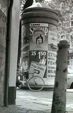 """Een reclamezuil mey op de voorgrond het paaltje genaamd een """"amsterdammertje"""""""