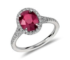 Beautifully unique, this ruby and diamond ring features an oval ruby surrounded by a halo of round diamonds and set in enduring platinum.
