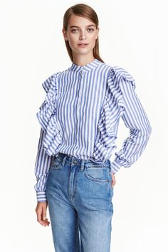 Blusa de volantes: Blusa en tejido de algodón con cuello elevado corto. Modelo con cierre oculto delante, hombros ligeramente caídos, mangas ligeramente anchas con botón en los puños y volante grande delante que continúa hasta media espalda.