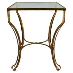 Curving open metal accent table with an antique gold finish and glass top.   Product: Accent tableConstruction Mater...