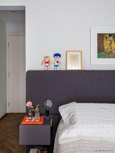 Quarto de casal clean com tons de cinza, preto e branco nos móveis e roupas de cama.