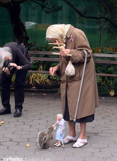 photo taken by Nathalie Kalbach of an 85-year old woman and her doppelgänger marionette feeding a squirrel in New York City's Washington Square Park .