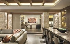 On the ground floor, the homeowner's office overlooks the family room and bar area, where designer Michael Fullen created a tailored sectional and upholstered it with Great Plains Thick as Thieves fabric. Magic Brown marble from Marbolis tops the bar.
