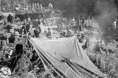 WWII troops use supply parachutes as tents while bivouaced in Burma rice paddy. Photographer Unknown