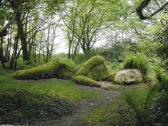 SLEEPING GODDESS AT THE LOST GARDENS OF HELIGAN, ENGLAND. The Lost Gardens of Heligan were created by members of the Cornish Tremayne family, over a period from the mid-18th century up to the beginning of the 20th century, and still form part of the family's Heligan estate. The gardens were neglected after the First World War, and only restored in the 1990s.