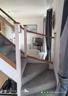 Oak rails with white newel posts and inline glass balustrade with a luxuriously soft carpet.