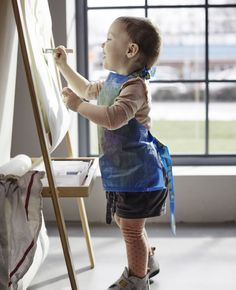 Ein Kind malt an einem MÅLA Stativ in Nadelholz/Weiß und trägt dabei eine Schürze, die aus FRAKTA Tasche in Blau gefertigt ist.