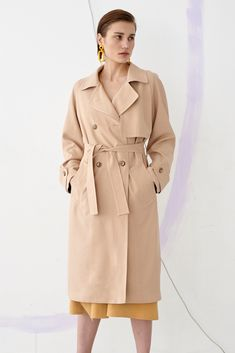 Double-breasted trench coat with a reglan, wide sleeve. Created on the basis of the Oslo model. It has an asymmetrical flap in the front. Fastened with buttons and tied with a belt in waist. On the sleeves there are straps with buttons. The coat has the form of the letter A, it is not fitted. Made of thick rayon fabric on a viscose lining. The colour of the coat is sunny sand beige.