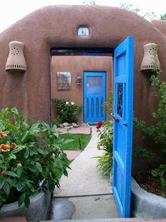 Paredes de adobe e brilhantes portas azuis que dao para um lindo jardim  com fonte.
