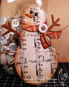 Snowman made from chipboard, old sheet music, paper for the scarf, an old button and some hemp twine. Oooh, and glitter!