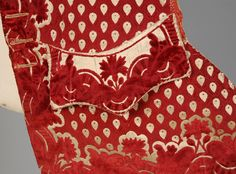 Detail pocket flap, waistcoat, Italy, 1765-1775. Cream and cranberry silk velvet having a repeat of inverted teardrop shapes bordered in a voided velvet floral, silk covered buttons, partially lined in silk and linen.