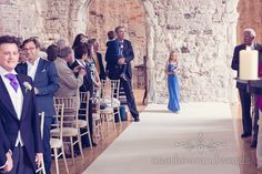 Bridesmaid in blue dress at Lulworth Castle wedding. Photography by one thousand words wedding photographers