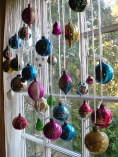 Hang christmas ornaments with ribbon off the curtain rod for a festive window…