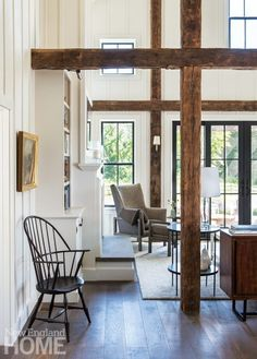 Beams from an eighteenth-century New Hampshire barn frame the view from the living room to the backyard.