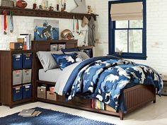 déco et aménagement chambre ado garçon - mur de brique blanche, couette à motif militaire bleu, boîtes de rangement métalliques et tapis tissé bleu