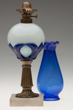 """TULIP AND STAR STAND LAMP, fiery opalescent and cobalt blue font, brass stem with stamped ornamentation, marble base, embossed on bottom of font """"PATENTED MARCH4 & JUNE3 1862"""", brass connector, No. 1 fine line collar. Fitted with a period set-up comprising a No. 1 hinged lip burner, period cobalt blue lip chimney with flattened sides and medium petal top. Atterbury & Co. Third quarter 19th century. 18 1/2"""" H to top of chimney, 10 5/8"""" H to top of collar,..."""