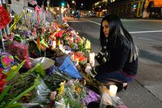 Ilka Reyes, of Orlando, Florida, who survived the Pulse nightclub shooting after being shot 9 times, adds flowers to the memorial for those killed in a Fruitvale district warehouse fire in Oakland, Calif., on Tuesday, Dec. 6, 2016. Reyes flew out to pay her respects to the 36 victims who lost their lives in the fire that started on Friday, Dec. 2. (Doug Duran/Bay Area News Group)