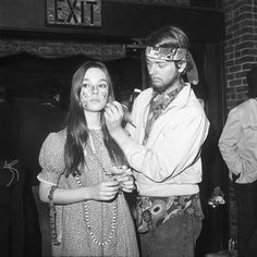 A woman has her face painted by a hippie friend in New York's Greenwich Village.
