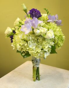 Green, purple and white bridesmaids bouquet. Including green hydrangea, purple lisianthus, lavender freesia and white spray roses.