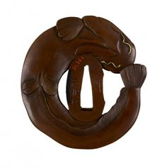 Tsuba with Catfish and Eel. This tsuba is made in the shape of a catfish. The fish is wrapped around the central opening so that that its mouth touches its tail at the upper left. On the catfish's back, at the right side of the tsuba, is an eel. Both catfish and eel are associated with summer. Iriyama Yoshitomo (Japanese, active ca. 1700-1750)