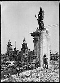 Vista desde lo alto de Palacio Nacional hacia la Catedral Metropolitana de México. Frontón o remate en el Palacio Nacional de México con un angel alado. Actualmente ya no existe. En la esquina del Zócalo o plaza de armas, se observa uno de los pegasos que se encuentran actualmente afuera en la explanada del Palacio de Bellas Artes. Imagen del siglo XX