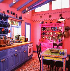 purple kitchen apartment. Fuchsia pink dresser in kitchen with bright blue fitted cupboards and  hand painted table chairs Purple cabinets a tiny glam All Things