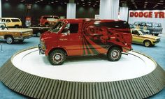 The Dodge truck and van exhibit at the 1980 Chicago Auto Show. The Dodge Ram Van show vehicle was painted a deep red and featured a stylized black four-legged ram charging across the body side, and causing graphic impact waves. Custom wheels were detailed in red to match the body.