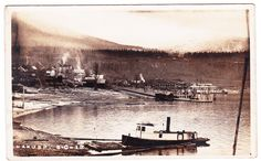"Photo postcard showing a view of Nakusp c.1900s-1910s. In foreground is the tug ""Smuggler"", along with the CPR SS Bonnington, Leland and Grand Hotels."