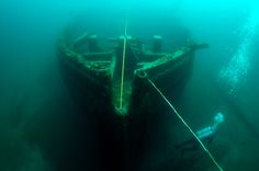 """Many of the more than 100 ghostly ships along """"Shipwreck Alley"""" in Thunder Bay National Marine Sanctuary appear through the eerie green water as if they might rise and set sail into the foggy horizon. Photo by Tane Casserley/NOAA, Thunder Bay NMS"""