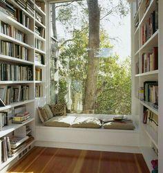 Window seat next to large window, bookshelf