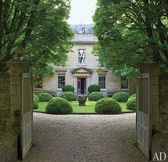 The main entrance gate of an English country estate opens to a view of its Georgian façade.