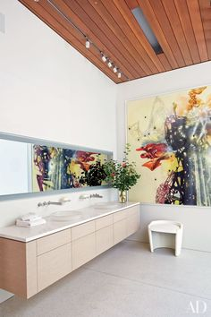 The architecture firm McRitchie Design collaborated with Gary Hutton Design on the renovation of collector Chara Schreyer's gallery-like Los Angeles home. A Matthew Ritchie painting makes a splash against the master bath's Corian walls; the Caesarstone-top vanity is equipped with Toto sinks and Lefroy Brooks fittings, and the stool was custom designed by Hutton.