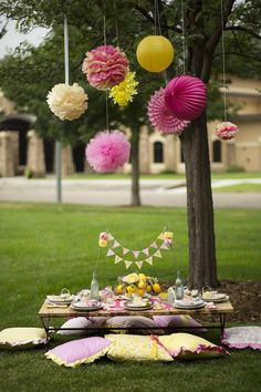 pink and yellow sunshine and sweet lemonade theme birthday party outdoor setting for table with tissue poms rosettes and paper lanterns hanging from the tree #outdoorpartythemes