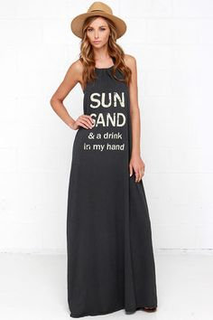 """Ready for a quick vacay? Take a step into the Brokedown Sun, Sand Washed Black Maxi Halter Dress and let it whisk you away to your own comfy paradise! Cotton knit forms an adjustable drawstring halter top above the words """"Sun Sand & a Drink in My Hand"""" in bold, faded print. Open back and maxi-length skirt. Unlined. 100% Cotton Modal. Machine Wash Cold. Made with Love in the U.S.A."""