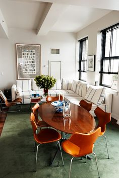 Inside Raden's Founder's Brooklyn Apartment: Blue and White Striped Couch, White Flowers, Tan Leather Chairs, Brown Wooden Table, Green Carpet | coveteur.com
