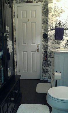 toile bathroom and ceramic tile that looks like wood floors.