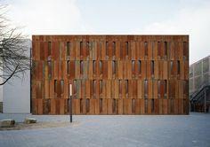 Haus der Essener Geschichte by Scheidt Kasprusch Architekten    The stripes of weathered steel panels are interrupted by angled recesses concealing narrow windows.