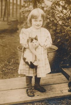 Portrait of a girl in a coat, hat, and muff, with her pet cat, ca ...