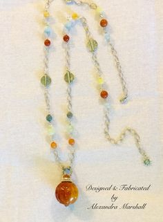 We love this colorful long occidental necklace with references to both Africa and Tibet by Alexandra Marshall. A large amber and rust colored Jade ball is suspended from antique silver chain links laced with blue Agates, , red Aventurine, Carnelian, yellow and green Jade. Custom Made for Bonnie. For details about a similar piece, double click photo to contact me via my website.