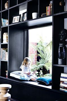 Black wall to wall built in bookcases with the perfect reading nook.