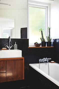 I love the mix of black tiles and wood. I'm really into natural light in bathrooms and the cacti top it off!